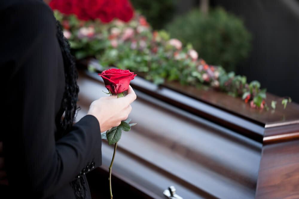 バラを持って棺桶の前に立つ女性