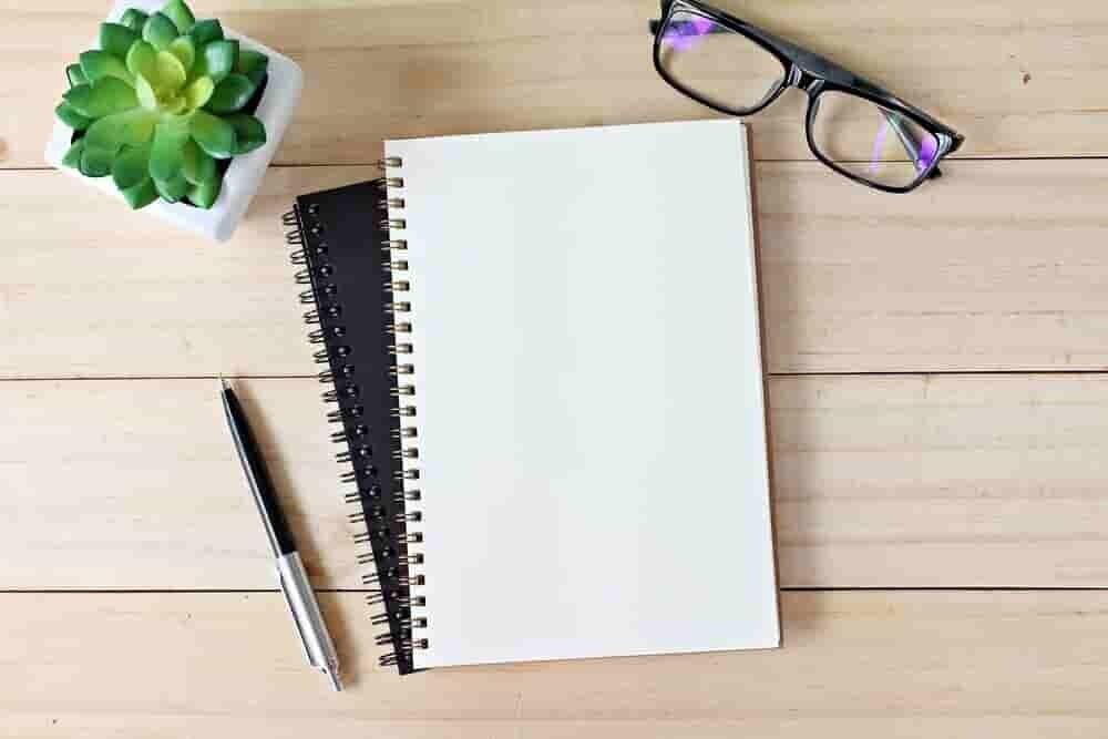 テーブルに置かれたノートとペンとメガネ