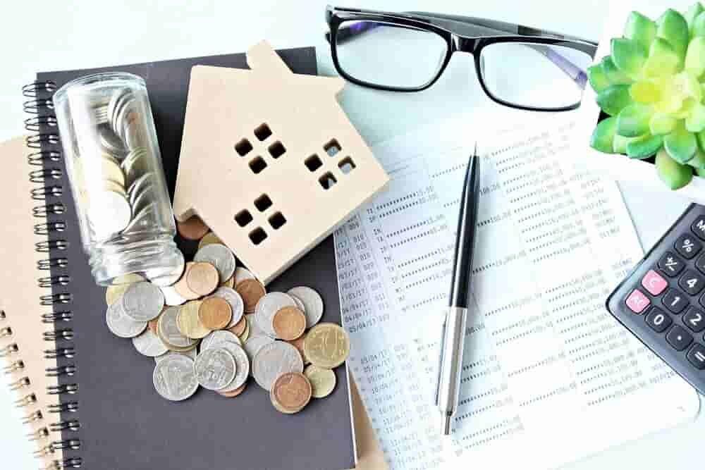 机の上にあるノートやペンと家の模型やお金