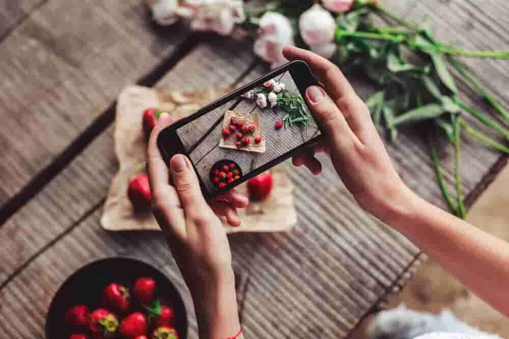 スマートフォンでイチゴの写真を撮る女性の手元