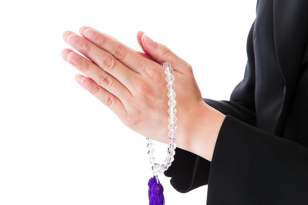 数珠を持って手を合わせる人