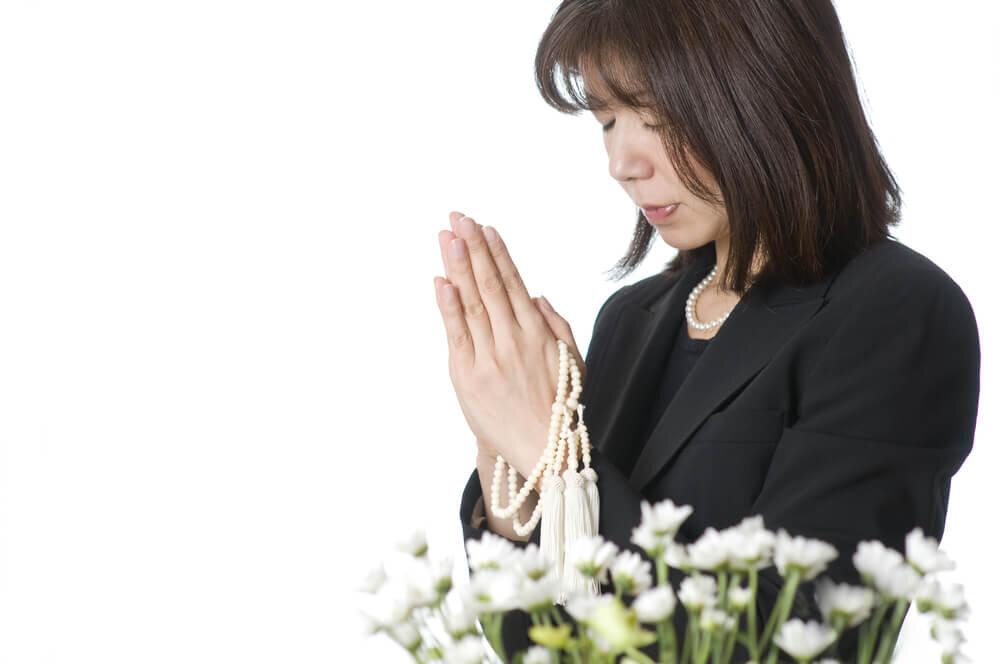 白い花のうしろで手を合わせる女性