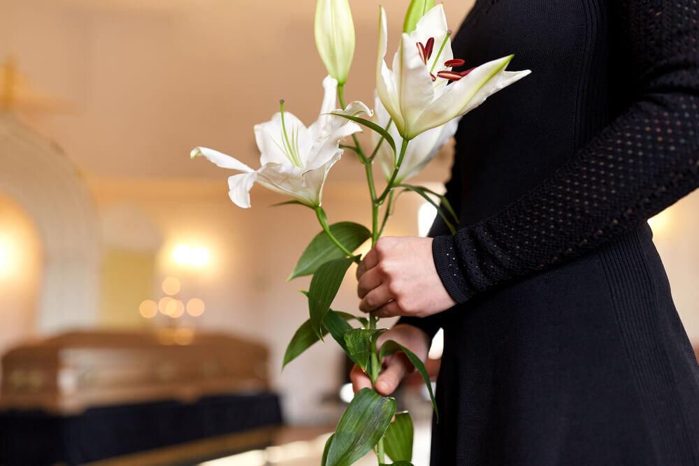 百合の花を持った喪服姿の女性