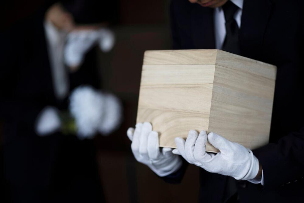 骨壺の入った箱を持ってお辞儀する人