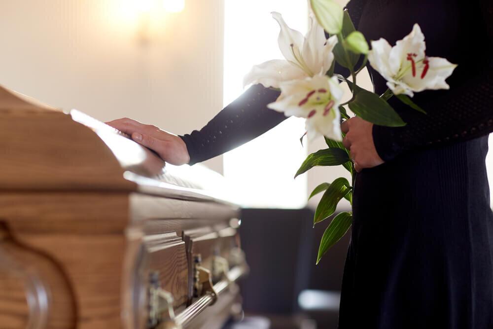 百合を持って棺に触れる女性