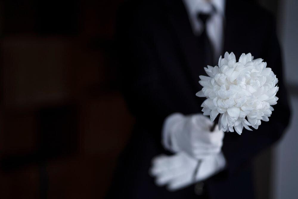 菊を持つ喪服の人