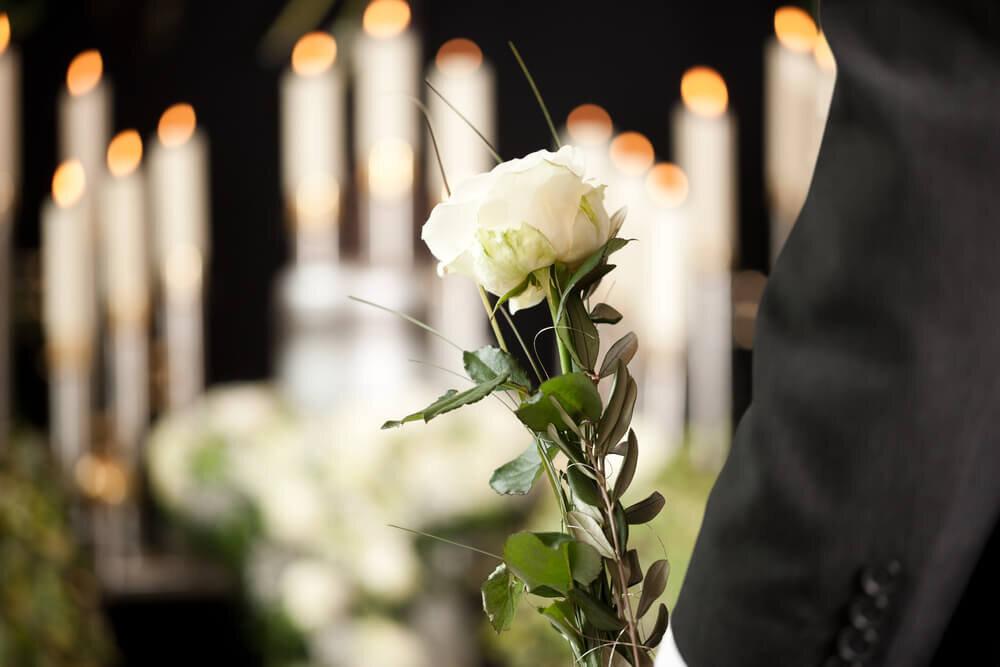 白い花を持つ男性