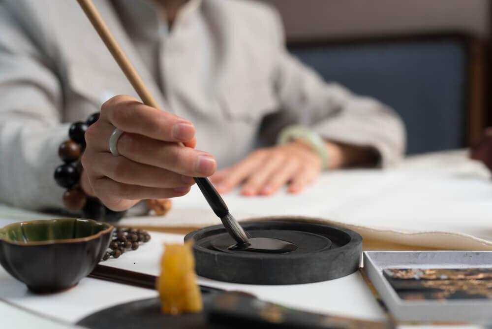 筆を持ち墨をつける人の手