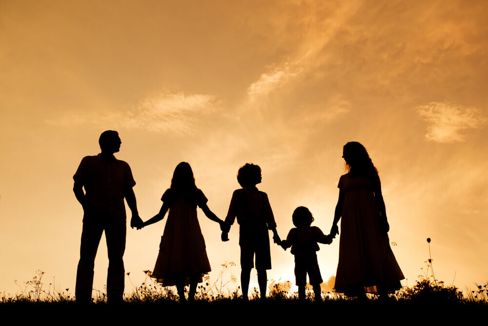 夕暮れの木の下で手をつなぐ家族のシルエット