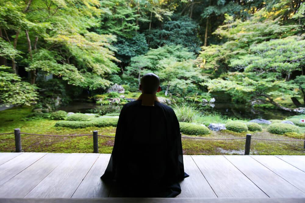 外を眺める僧侶