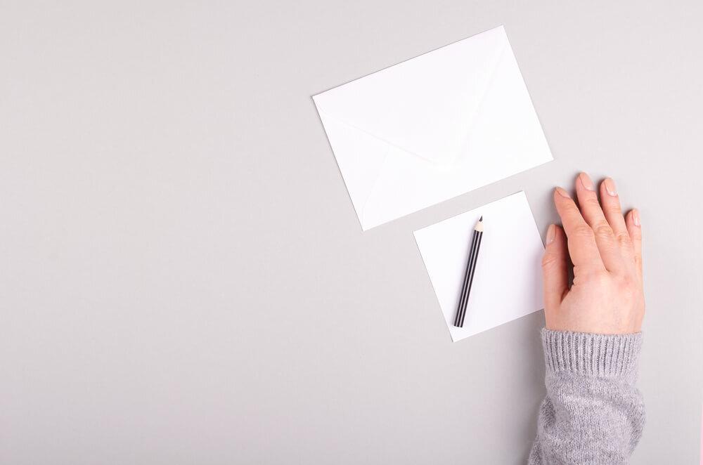 手紙と鉛筆のそばに置かれた手