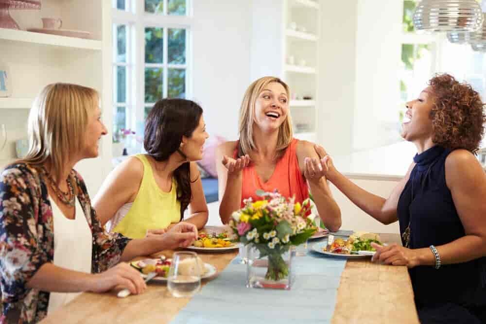 笑いながら食卓で会話をする女性