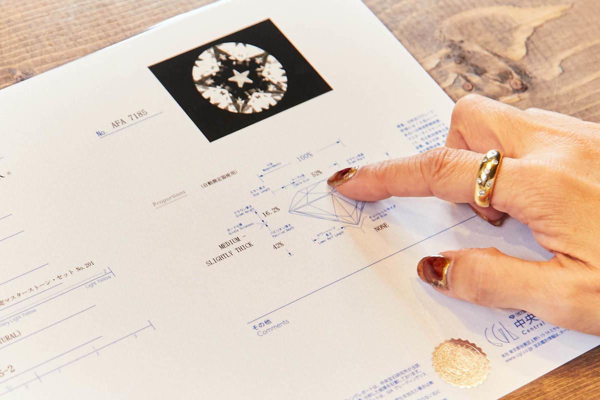 ダイヤモンドのグレーディングレポートを指差すフェスタリアのジュエリー鑑定士:新保薫