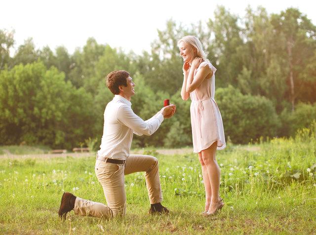 ひざまづいてプロポーズする男性と喜ぶ女性