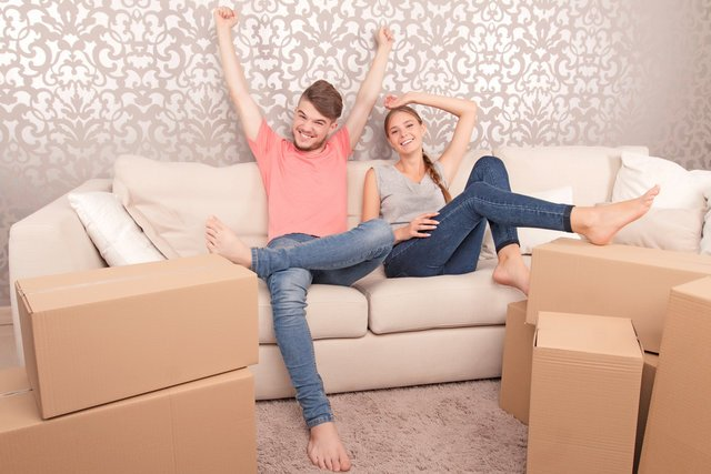 引っ越し後に段ボールに囲まれて笑顔を見せるカップル