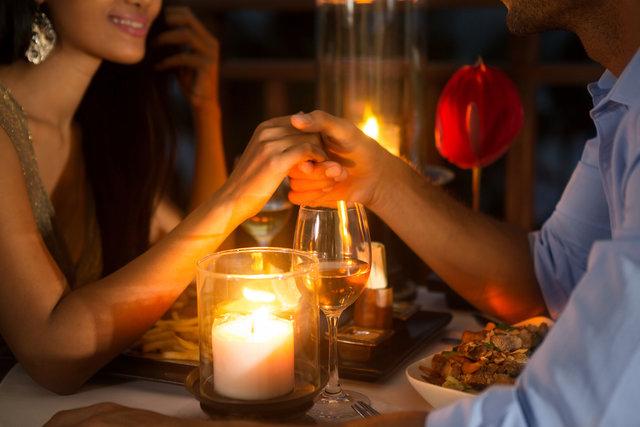 ロマンチックなディナーで女性の手を握る男性