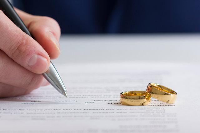 結婚に関する書類を書く手と二つの指輪