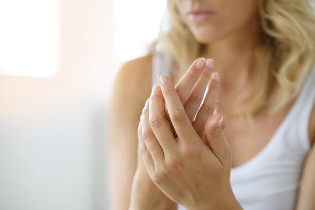指のむくみを気にしている女性