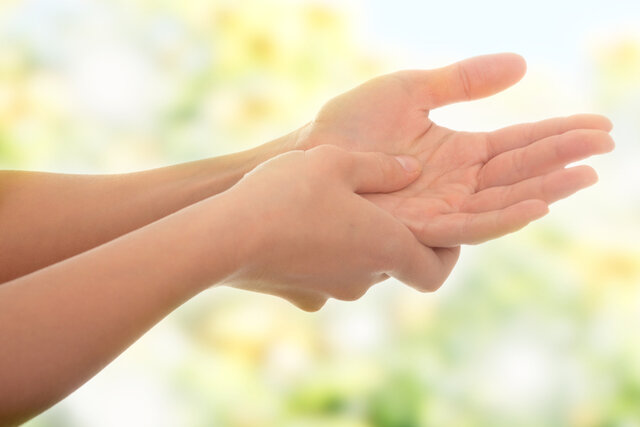 手のツボ押しをしている女性の手
