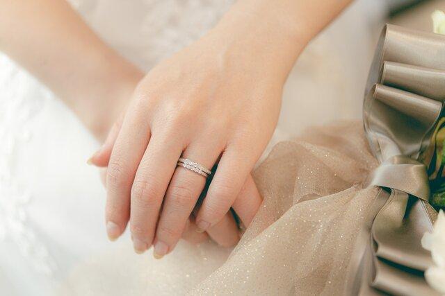結婚指輪を身に着け手を重ねる女性