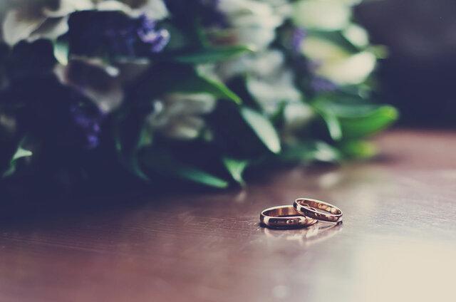 花束とともに机に置かれた結婚指輪