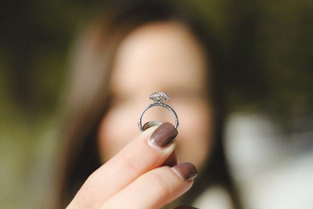 エンゲージリングを指で持つ女性