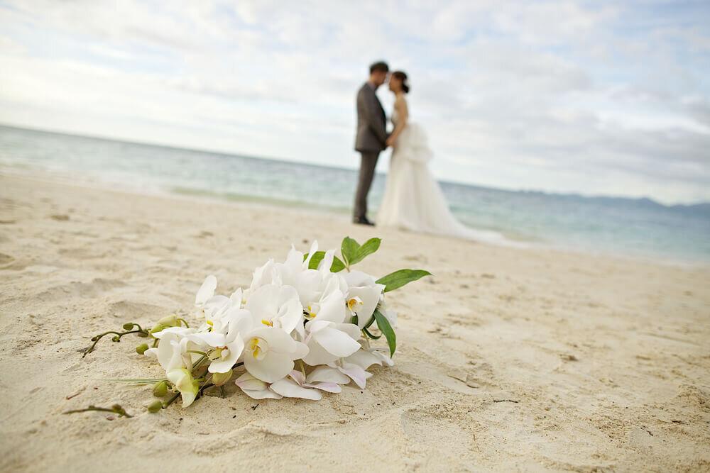 海辺で結婚式を挙げるカップル