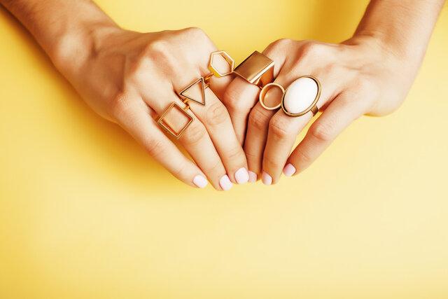 いろいろな指にリングを着けた女性の手