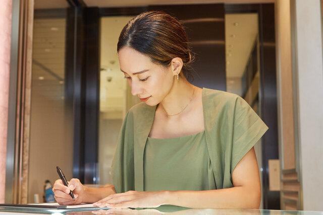 店頭でオーダーメイドジュエリー専用の用紙に記入する女性