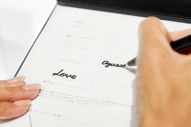 専用の用紙にジュエリーにしたい文字を記入する様子