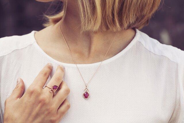 ガーネットのリングとネックレスを着ける女性
