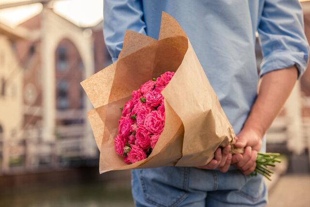 花束を持つ男性のうしろ姿