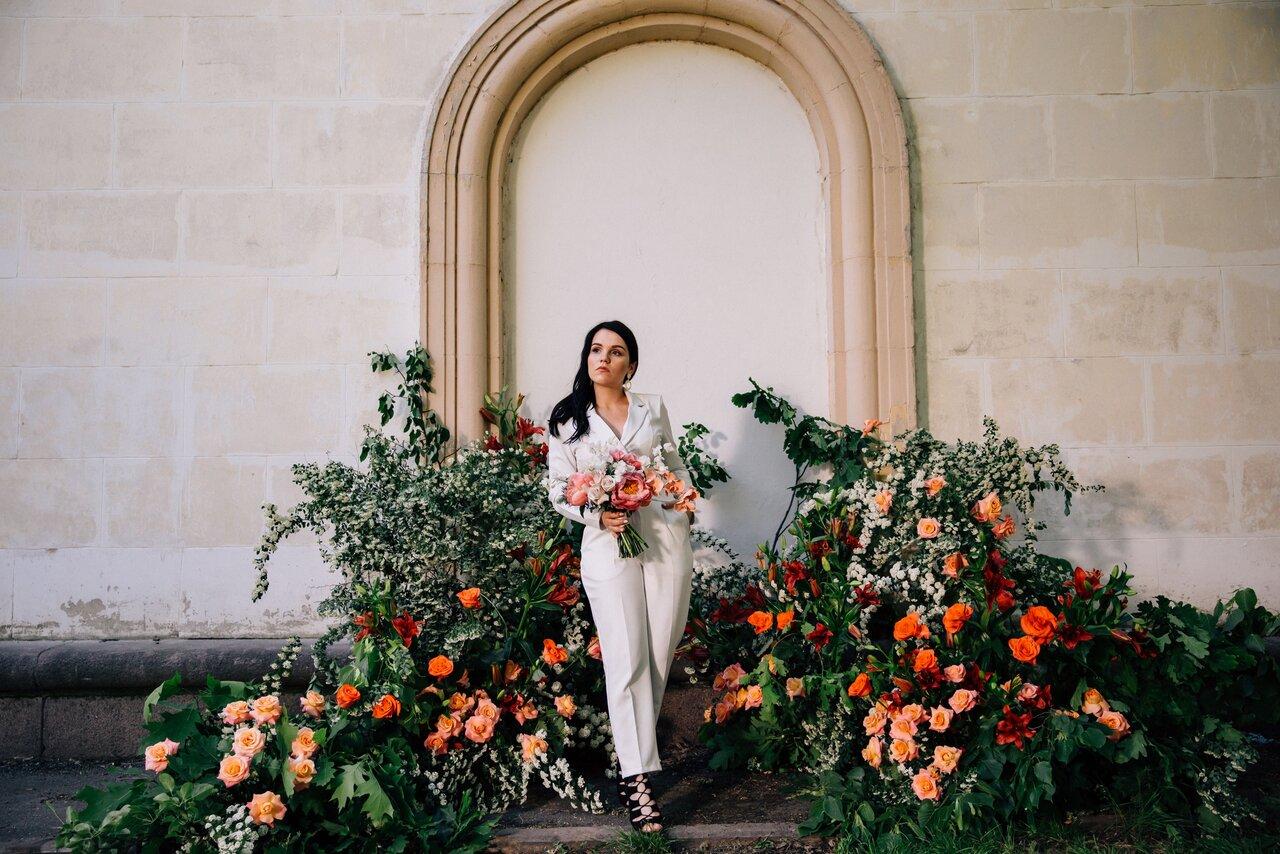 パンツスタイルの花嫁が庭に立つ様子