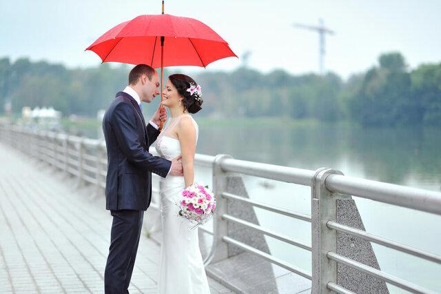 赤い傘をさした新郎新婦
