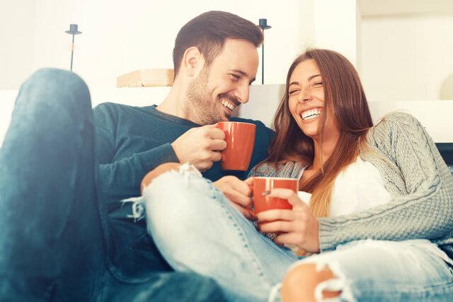 ソファでコーヒーを飲むカップル