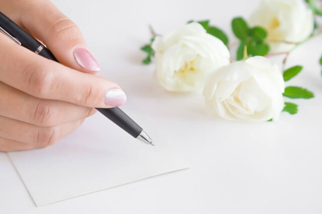 カードにメッセージを書く女性の手