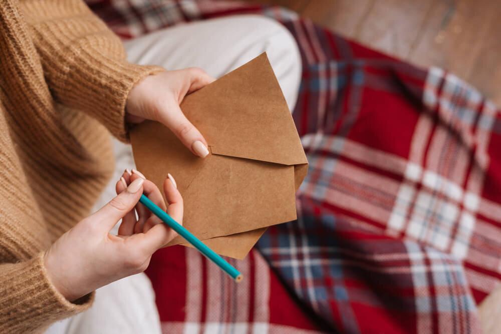 封筒とペンを持つ女性