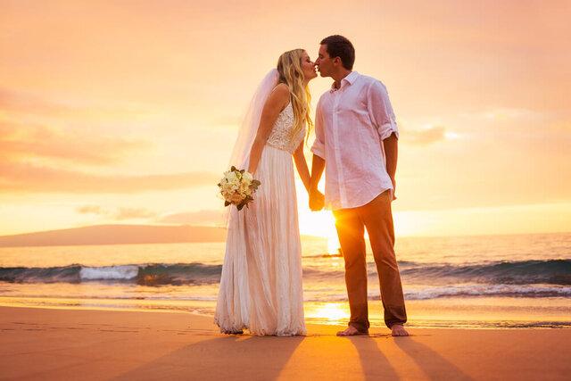 夕暮れ時の海で結婚するカップル