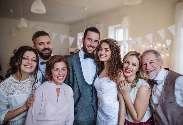 家族と並んで微笑むカップル