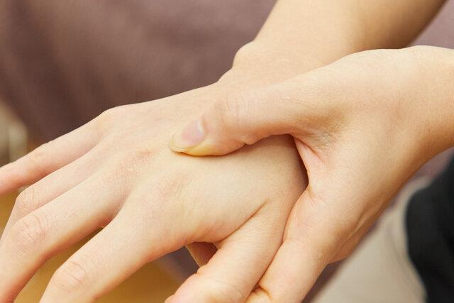 親指で手の甲をなぞる
