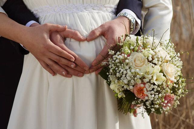 妊婦の花嫁のお腹に手を添える新郎