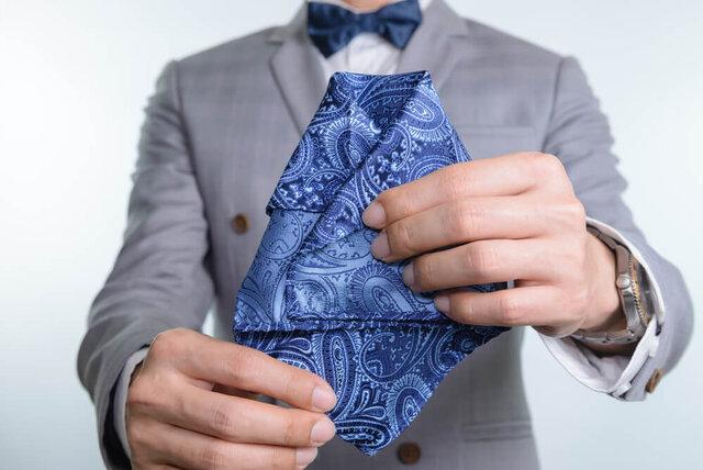 ポケットチーフを折る男性