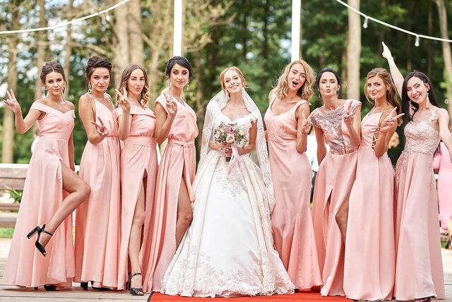 ピンクの衣装のブライスメイドに囲まれた花嫁