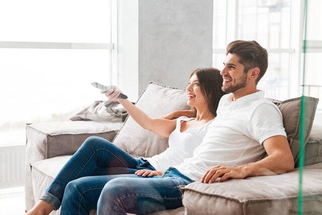 ソファに座ってテレビを見るカップル