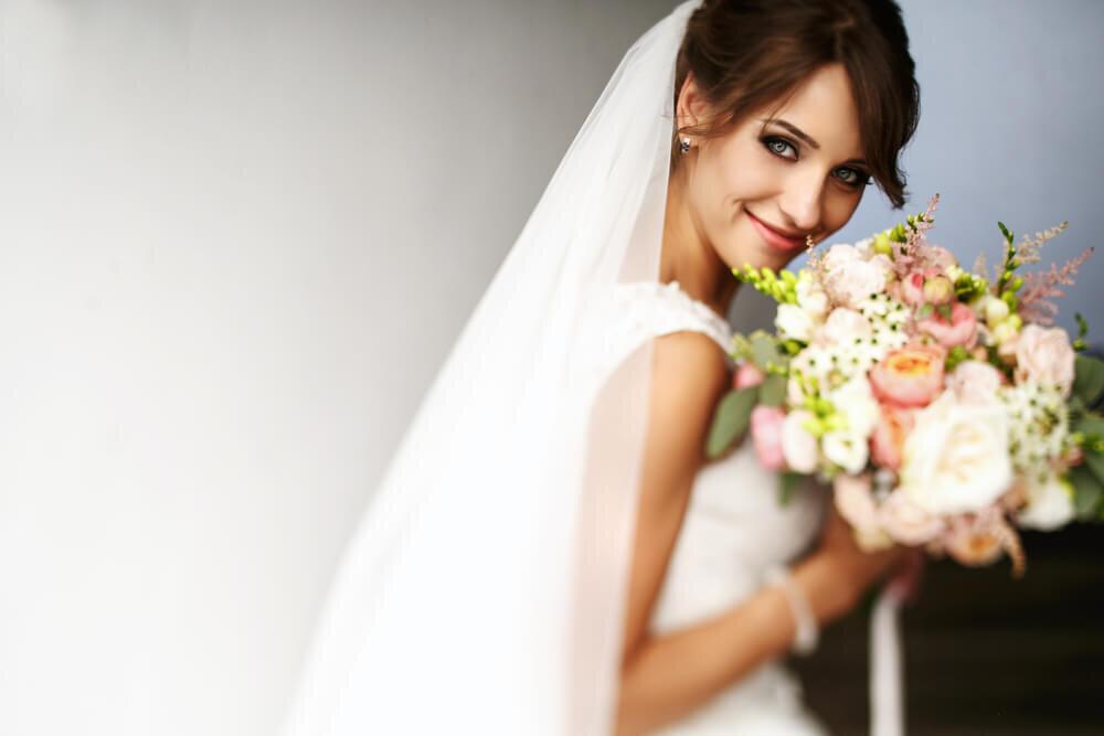 バラの花束を持って笑顔の花嫁