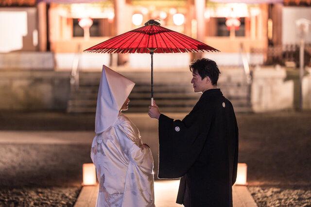 和装で傘をさす新郎新婦