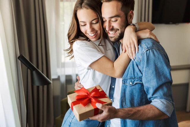 プレゼントを持って抱き合うカップル