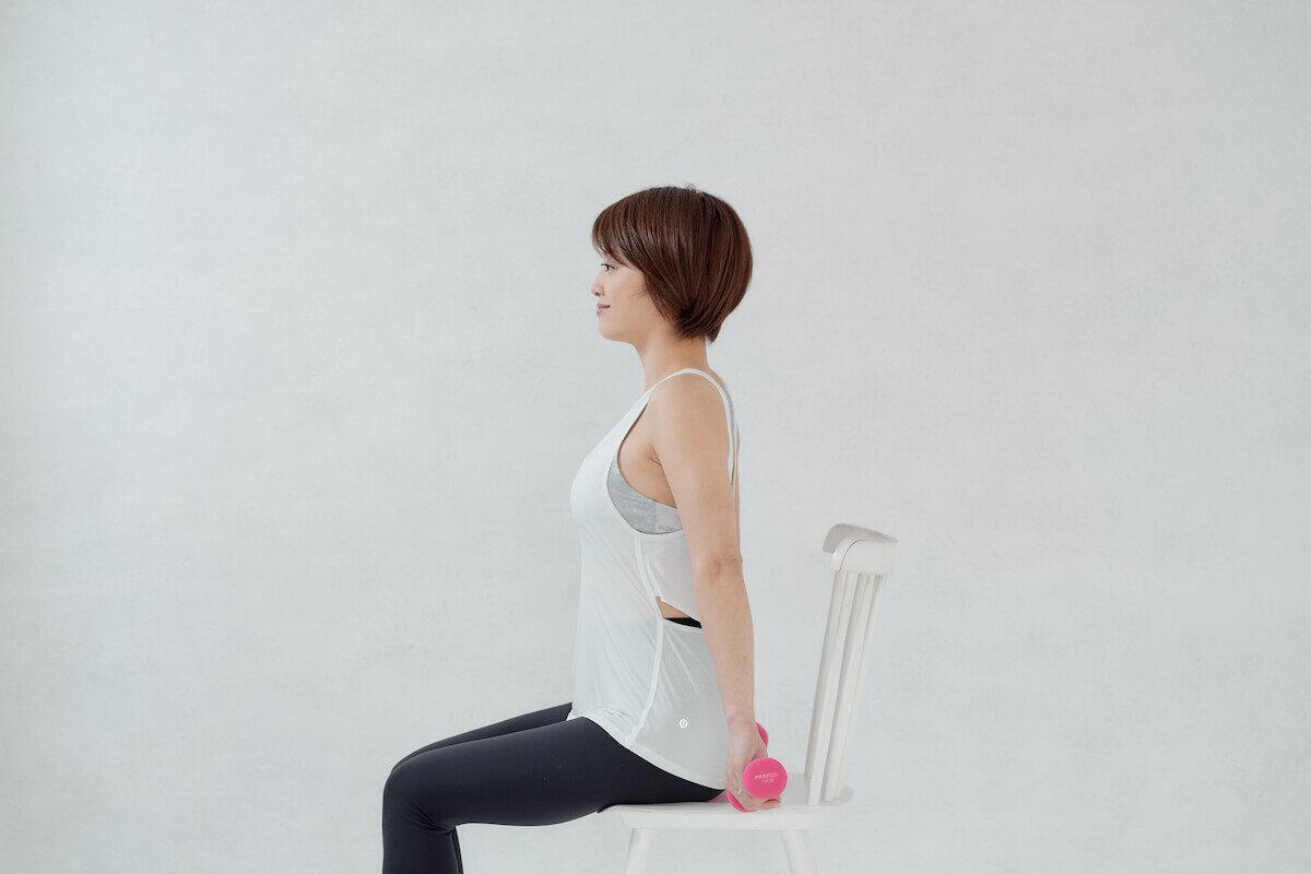 椅子に座ってウエイトを持つChiekoさん