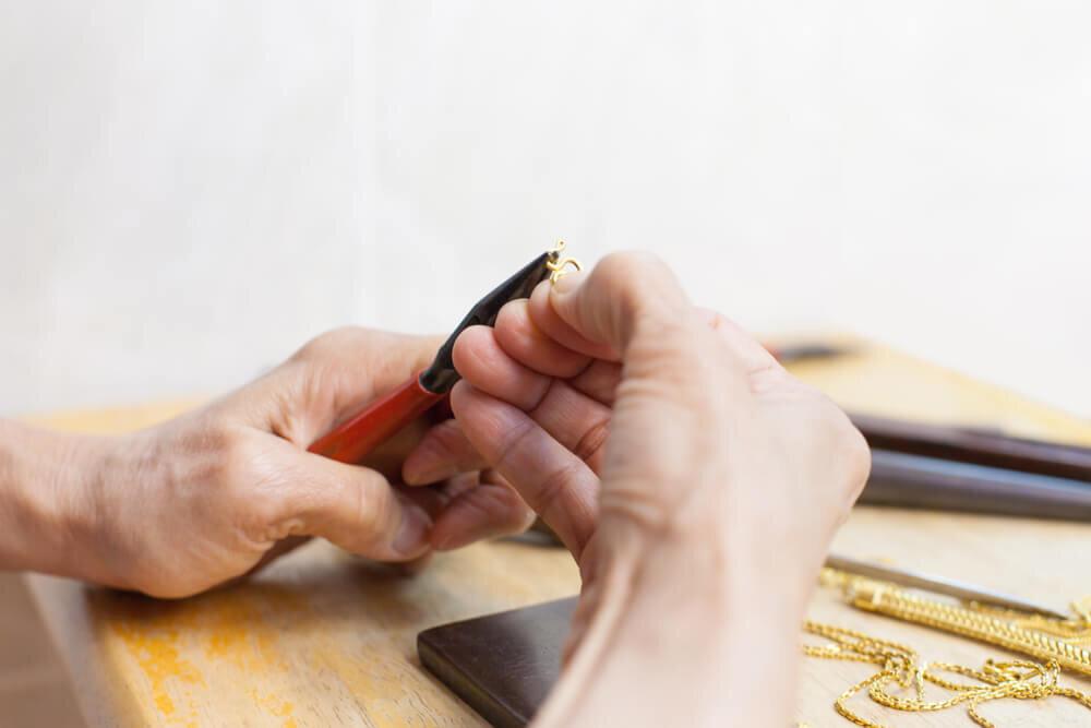 ペンチでネックレス修理をする人