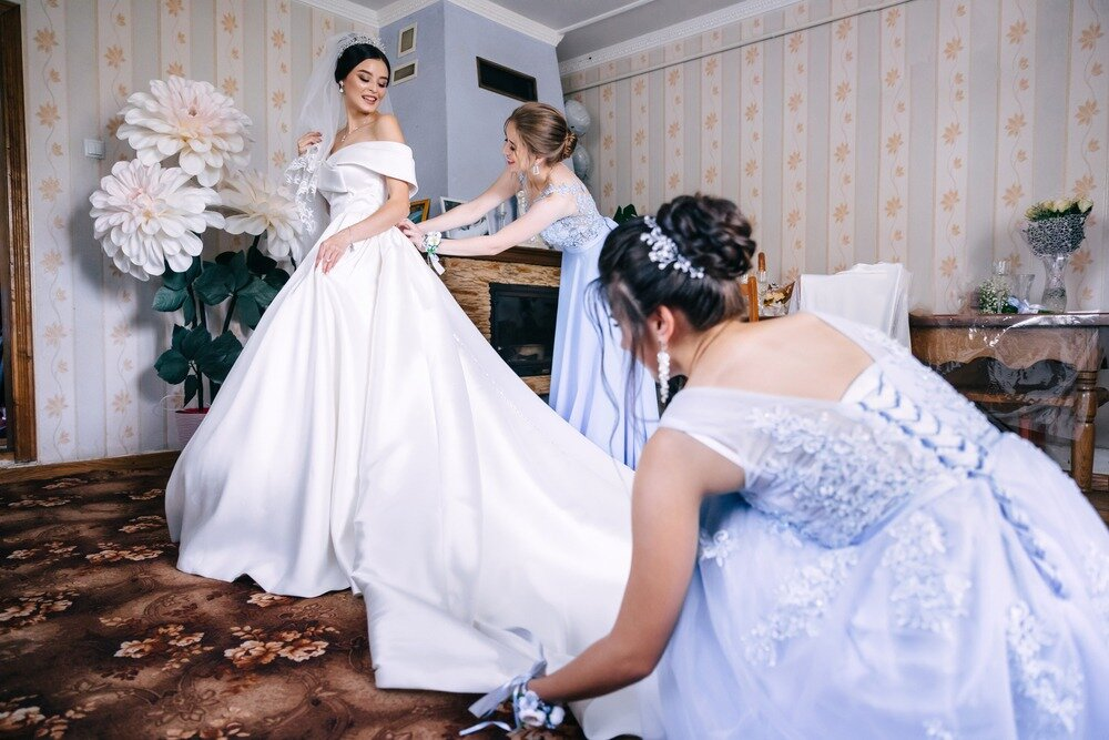 友人達に着替えを手伝ってもらっている花嫁